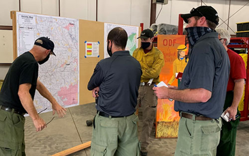 Photo of Incident Management Team personnel studying a wildfire map in Oregon